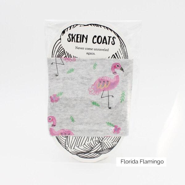 """Présentation du Skein Coat """"Florida Flamingo"""" de Precious Knits à motifs de flamants roses et de fleurs roses sur fond gris clair"""