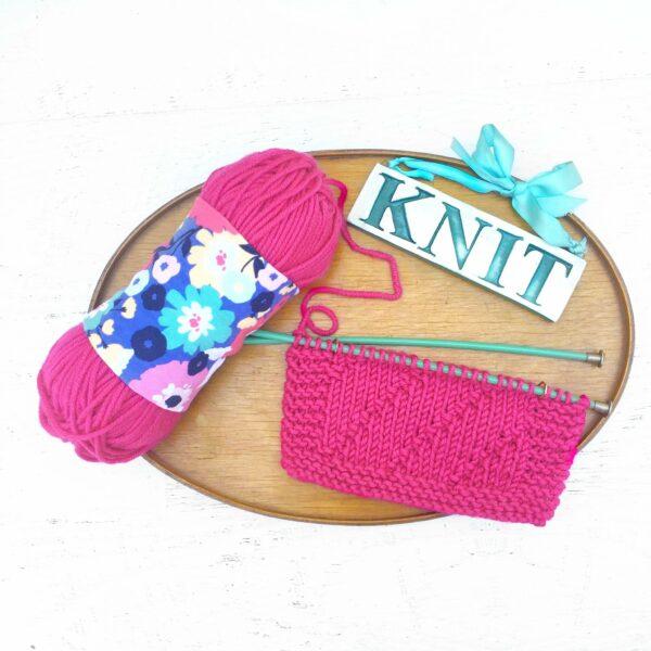 Présentation d'un Skein Coat de Precious Knits, à motif Spring Poppy, autour d'une pelote de laine rose