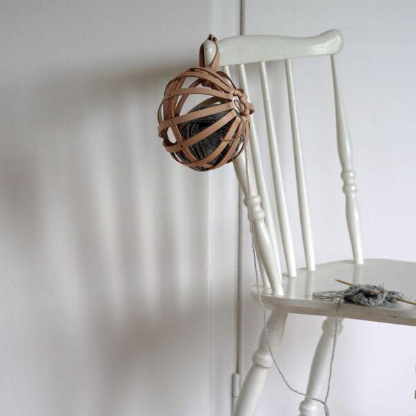 Un Cocoon de Geo-metry coloris Tan présenté sur une chaise avec un projet en cours