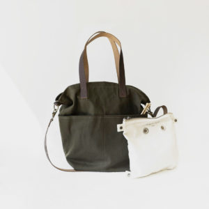 Display of a canvas Crossbody bag by Twig & Horn, in the Olive colorway, with its assorted project bag