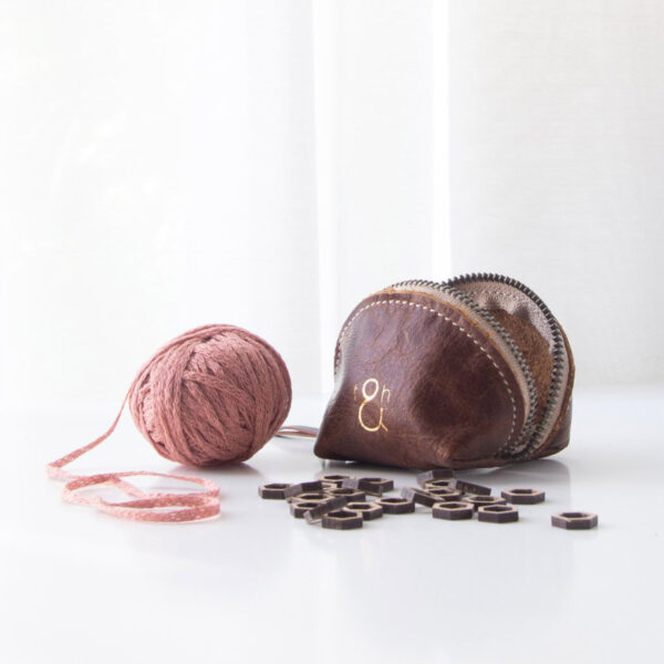 Display of a dumpling leather pouch by Twig & Horn next to a pink ball of yarn and markers