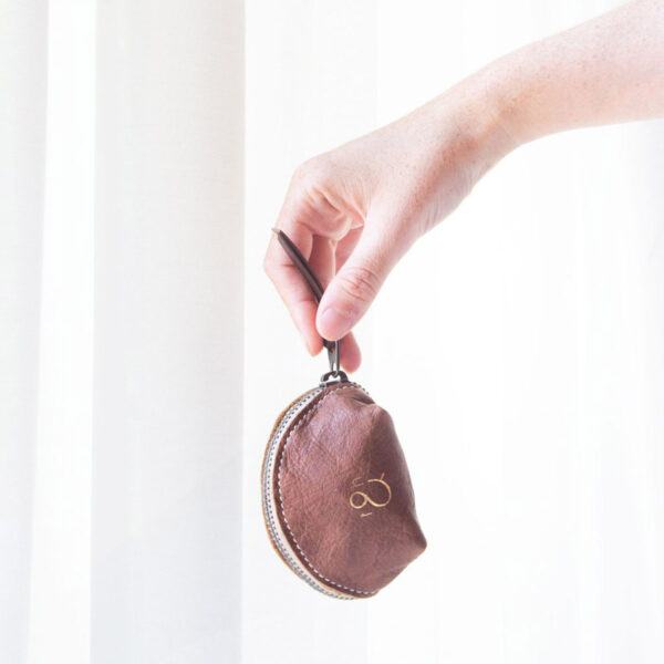 """Display of a """"dumpling"""" leather pouch by Twig & Horn, held in a hand (for size)"""