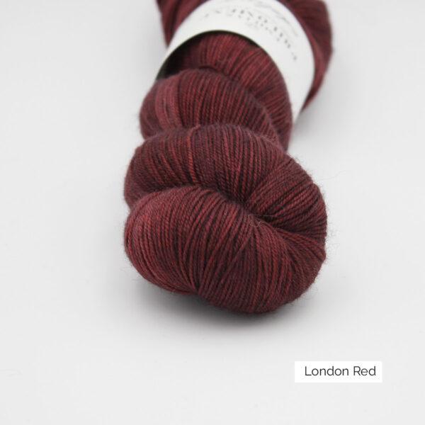 Gros plan sur un écheveau d'Adelina d'Emilia & Philomène coloris London Red (rouge foncé nuancé)