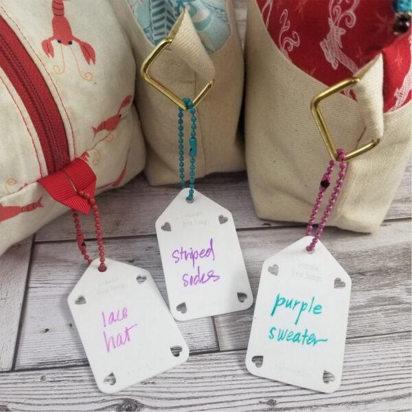 Présentation de trois étiquettes effaçables pour sac à projets de la marque Katrinkles