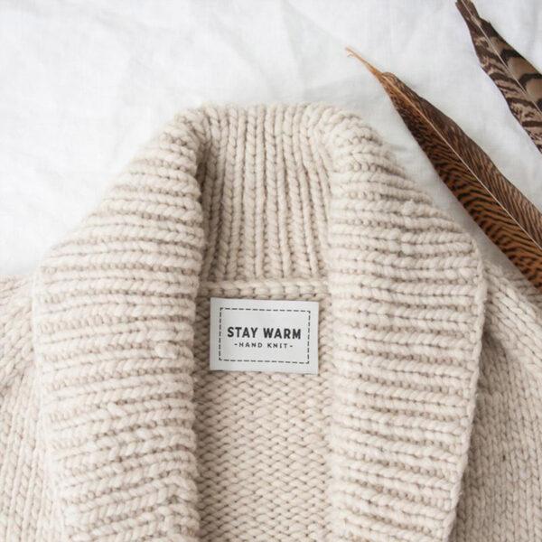 Présentation d'une étiquette pour tricot à coudre Stay Warm de Twig & Horn sur un gilet en laine