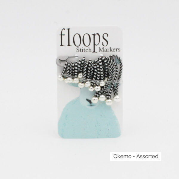 A card of flexible Floops Stitch Markers in the Okemo colours (checkered black and white) and assorted sizes