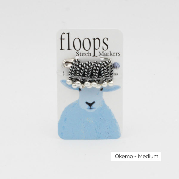 A card of flexible Floops Stitch Markers in the Okemo colours (checkered black and white) and medium size