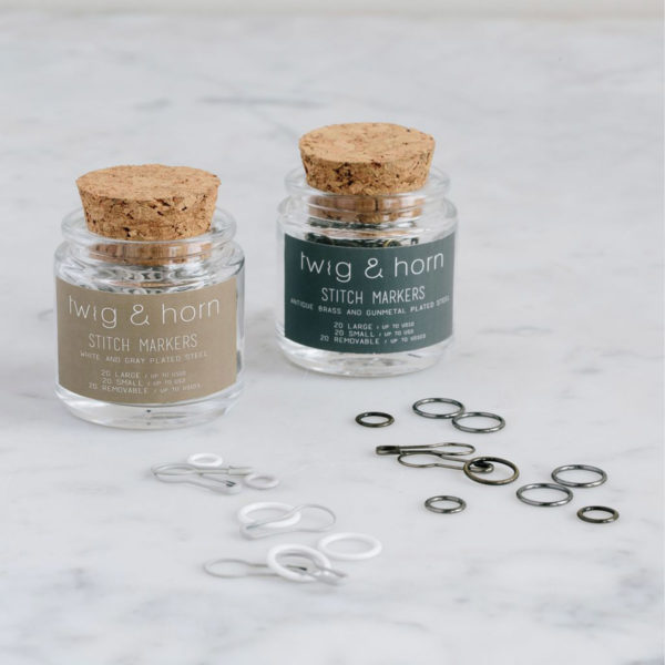 Display of two glass vials with a cork stopper that contain Twig & Horn stitch markers