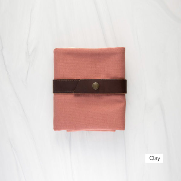 Display of a Twig & Horn interchangeable needle case in the Clay colorway, made of orangey-pink canvas and brown leather, closed