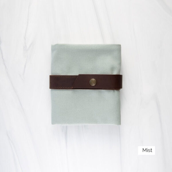 Display of a Twig & Horn interchangeable needle case in the Mist colorway, made of light grey-green canvas and brown leather, closed
