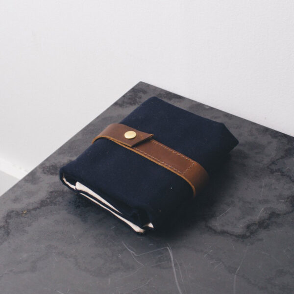 Display of a Twig & Horn interchangeable needle case, made of navy canvas and camel leather, closed