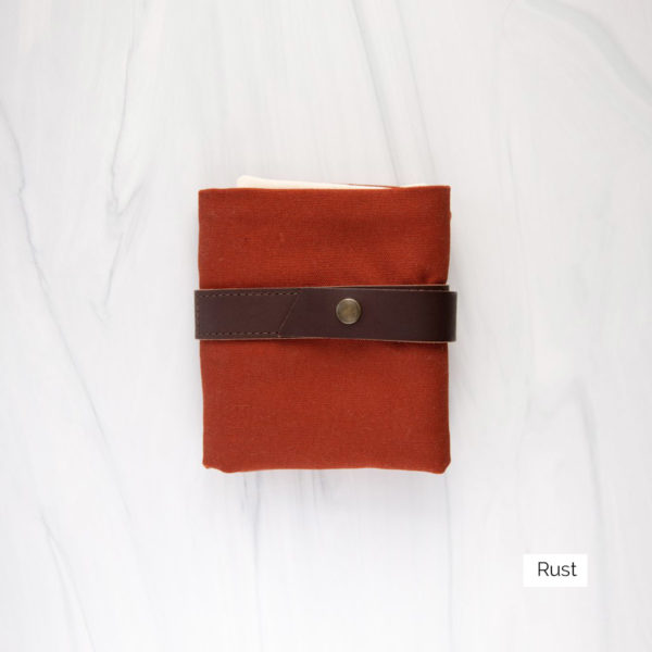 Display of a Twig & Horn interchangeable needle case in the Rust colorway, made of reddish orange canvas and brown leather, closed