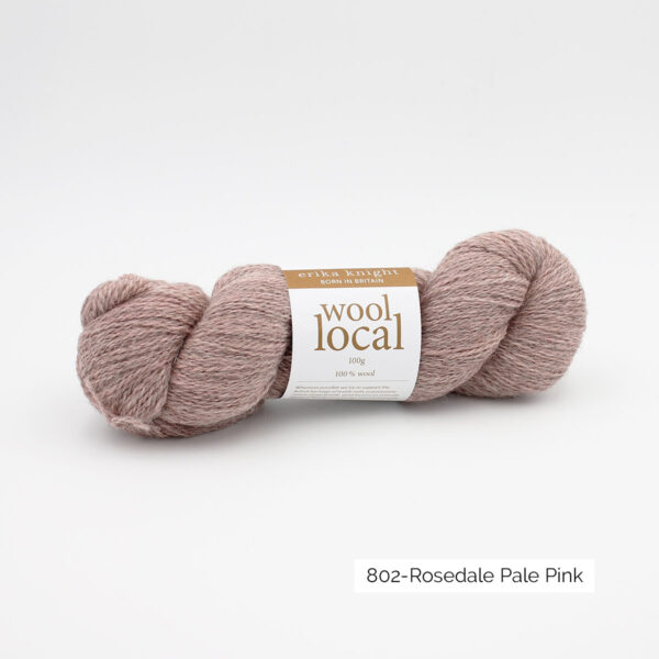A skein of Erika Knight's Wool Local in the Rosedale Pale Pink colorway (greyish light pink)