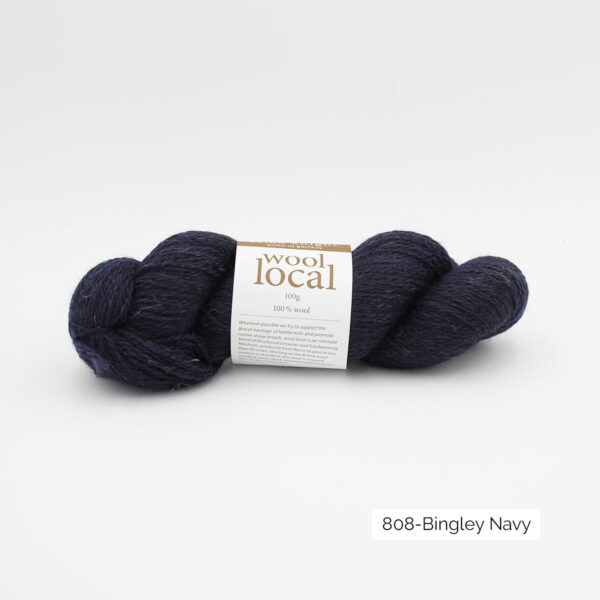 A skein of Erika Knight's Wool Local in the Bingley Navy colorway (heathered marine blue)
