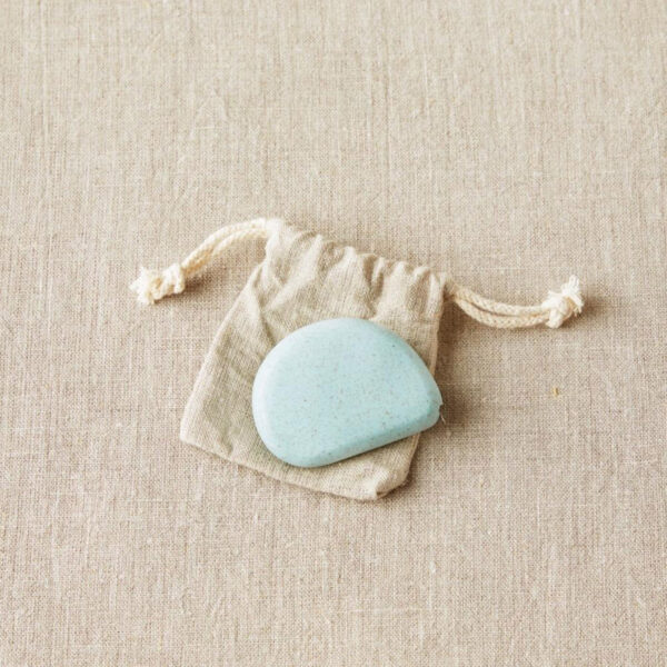Display of a retractable and eco-friendly tape measures, designed by Cocoknits, in its linen pouch, in the Sea Glass colorway, a minty green colour