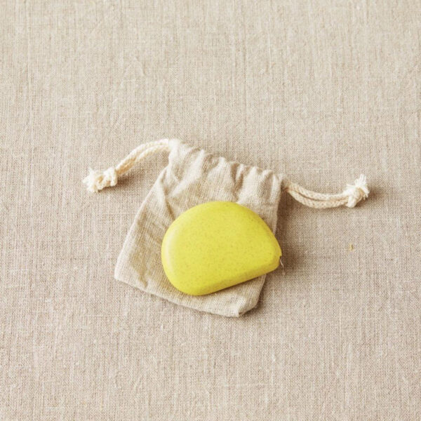 Display of a retractable and eco-friendly tape measures, designed by Cocoknits, in its linen pouch, in the Mustard Seed colorway, a sunny yellow colour