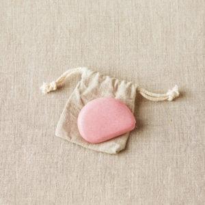 Présentation d'un mètre ruban rétractable eco-friendly Cocoknits de couleur rose et de son sac de rangement en lin