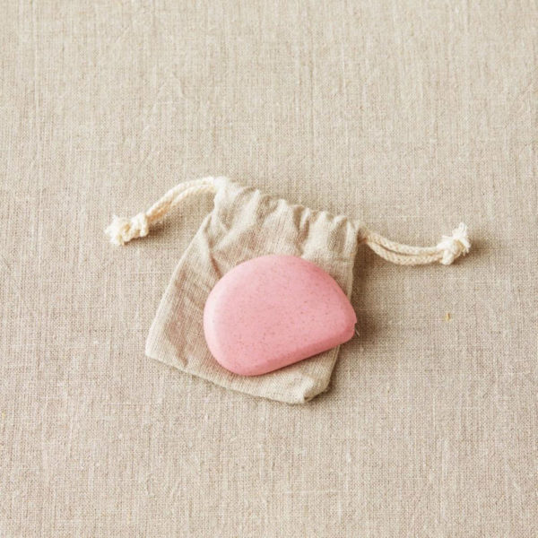 Display of a retractable and eco-friendly tape measures, designed by Cocoknits, in its linen pouch, in the Wild Rose colorway, a pastel pink colour