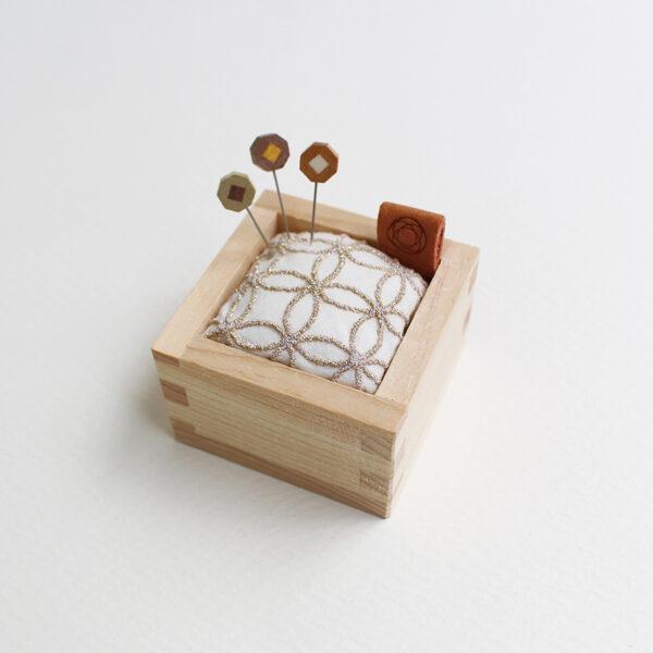Présentation du coussin pique-aiguilles et de ses épingles à tête en bois marqueté de l'édition spéciale de noël de Cohana