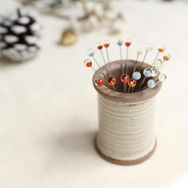 Présentation d'une bobine aimantée porte-épingles en céramique Hasami de l'édition spéciale de noël de Cohana