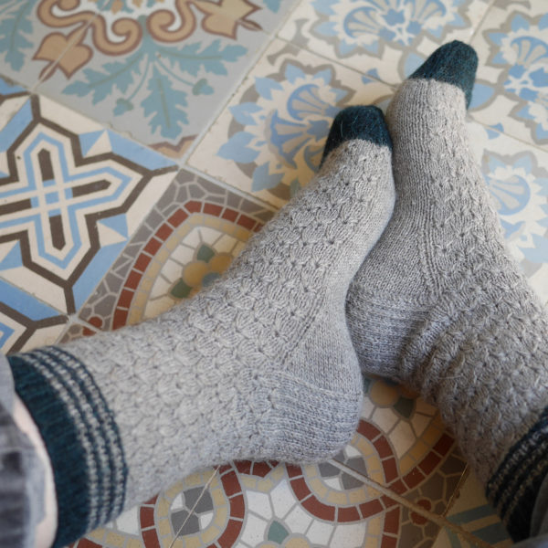 Présentation d'une paire de chaussettes du modèle Hafer d'Emma Ducher tricotées en Amble de The Fibre Co. portées
