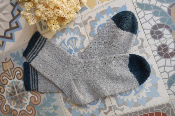Présentation d'une paire de chaussettes du modèle Hafer d'Emma Ducher tricotées en Amble de The Fibre Co.