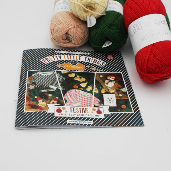 A view of the Pretty Little Things magazine cover and the balls of yarn included in the Santa Claus socks kit