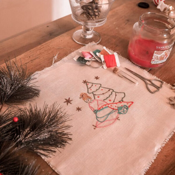 Display of Elodie Blueberry's Christmas embroidery kit, presented laying flat with spools of threads, a pair of scissors and a Katrinkles needle minder