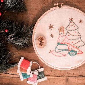 Display of Elodie Blueberry's Christmas embroidery kit, presented in an embroidery hoop with spools of threads and a Katrinkles needle minder