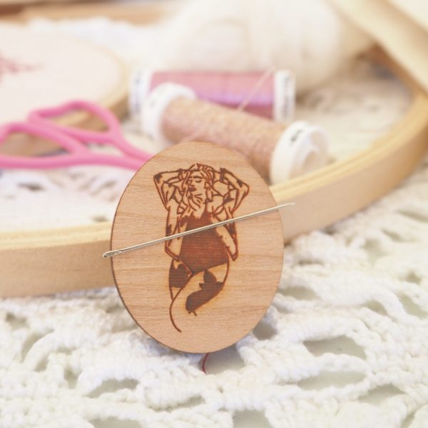 Display of a wooden needle minder engraved with a woman's sexy figure