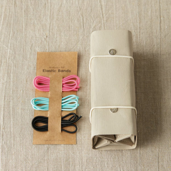Présentation d'un Accessory Roll de Cocoknits coloris gris, roulé et fermé, avec ses élastiques de couleur