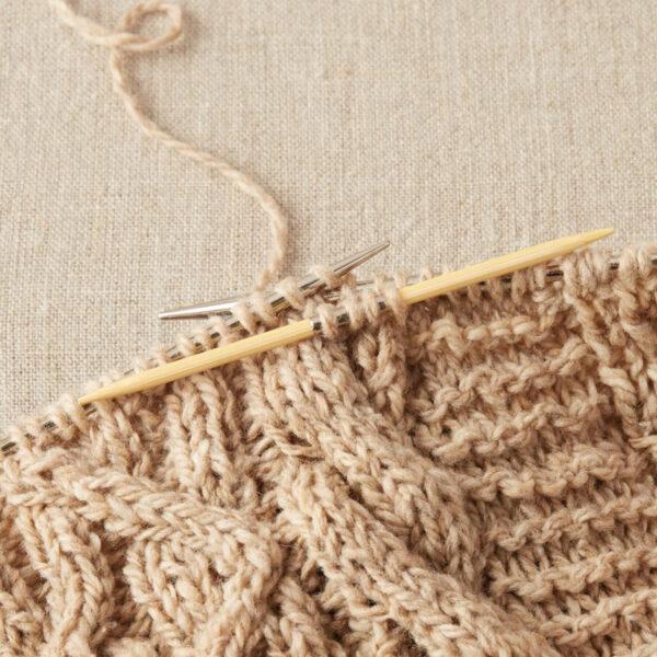 Présentation d'une aiguilles à torsades en bambou de la marque Cocoknits sur un en-cours de tricot