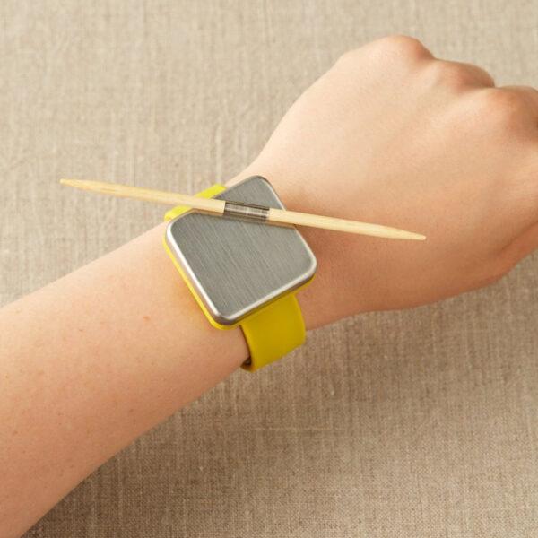 Présentation d'une aiguille à torsades en bambou de la marque Cocoknits portée sur le bracelet magnétique de la marque