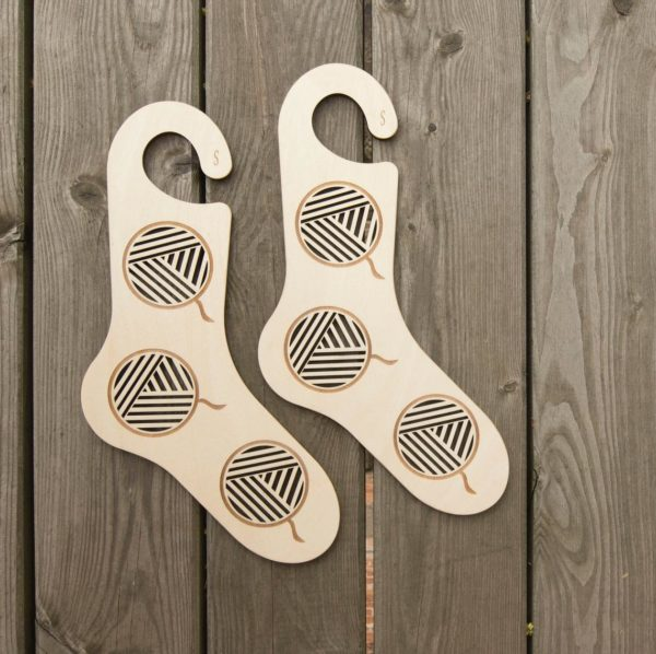 Présentation d'une paire de bloqueurs de chaussettes en bois au motif ajouté de pelotes de laine