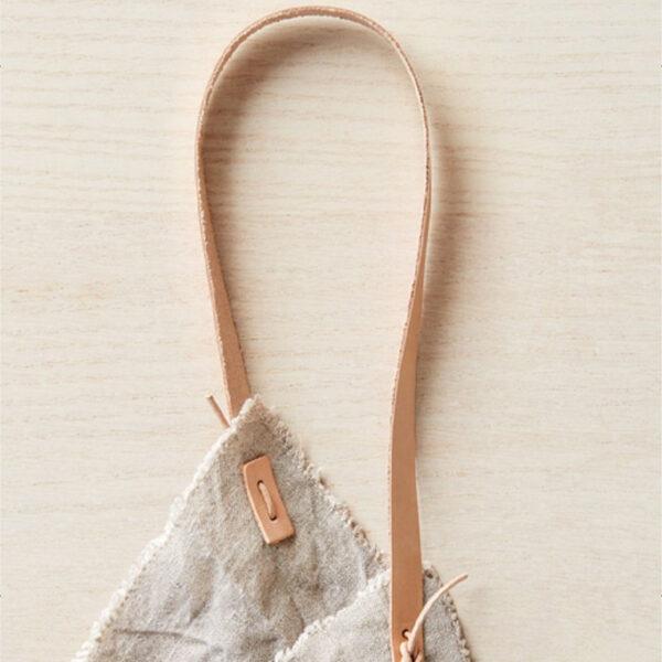 Présentation d'un set de poignées en cuir pour sac de la marque Cocoknits posé sur un sac en lin brut