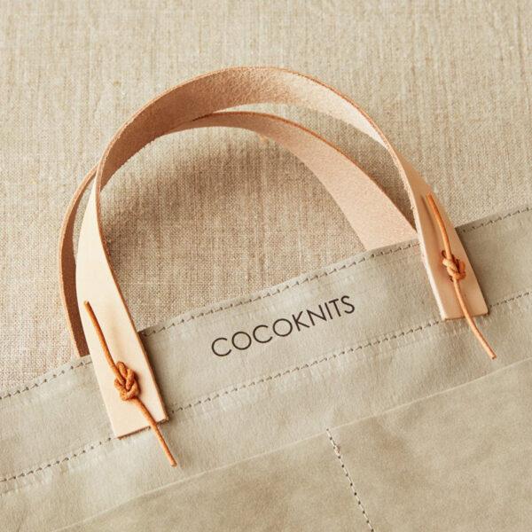 Présentation d'un set de poignées pour sac en cuir de la marque Cocoknits posé sur un Kraft Caddy de la marque
