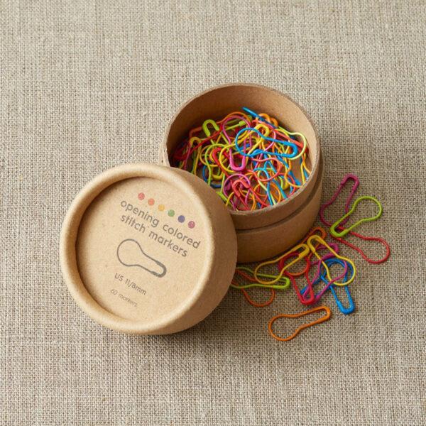 Présentation d'une série de marqueurs de mailles amovibles forme ampoule aux couleurs de l'arc-en-ciel de la gamme Colored Opening Stitch Markers de Cocoknits dans leur boîte de rangement