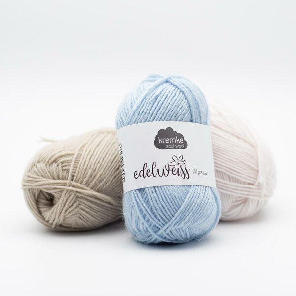 Présentation de trois pelotes de laine à chaussettes Edelweiss Alpaca 25 de Kremke Soul Wool dans des coloris assortis