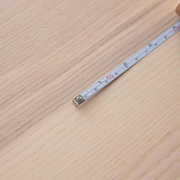 Gros plan sur la double numérotation en centimètres et en inches du mètre ruban à boîtier en bois Twig & Horn